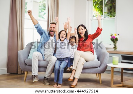 Full length of happy family cheering while siting on sofa at home #444927514