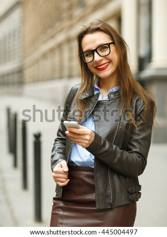 Businesswoman walking down the street while talking on smart phone. Happy smiling caucasian business woman busy #445004497