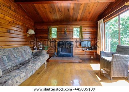 Cozy interior of a rustic log cabin with a fireplace. #445035139