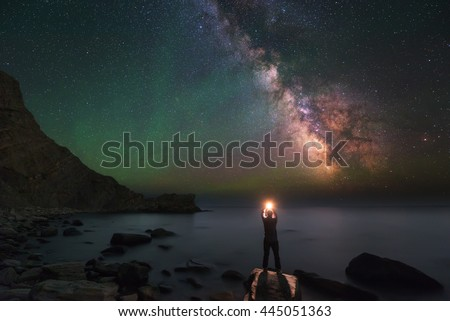 Man and Universe, shore of the ocean, sea, fire and stars in hands, in palms, igniting stars, Inspiration photo, unity the man and universe, astronomy and astrophotography, Milky Way, green airglow #445051363