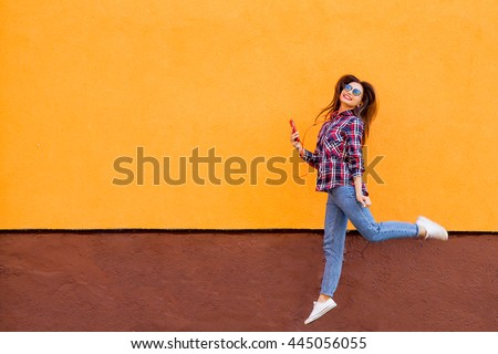 Fashion portrait of pretty smiling and jumping woman in sunglasses with smartphone against the colorful orange wall. Copyspace #445056055