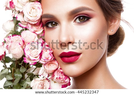 Portrait of young beautiful woman with stylish make-up and colorful roses around her face #445232347