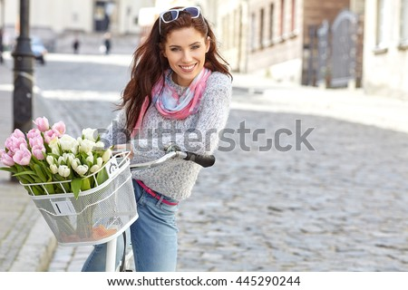 Woman wearing a spring skirt like vintage pin-up holding bicycle with some yellow flowers in the basket in old town