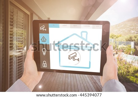 Cropped hand of man holding digital tablet against stylish outdoor patio area #445394077