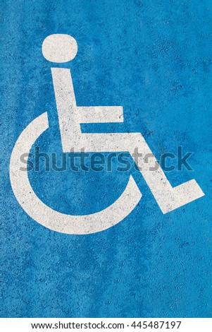Blue handicap parking sign on asphalt for persons with disability #445487197