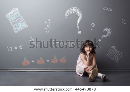 Adorable child with problems in math. Dreaming little girl sits on the floor. Big question marks, examples and book are depicted with chalk in the neutral background.
