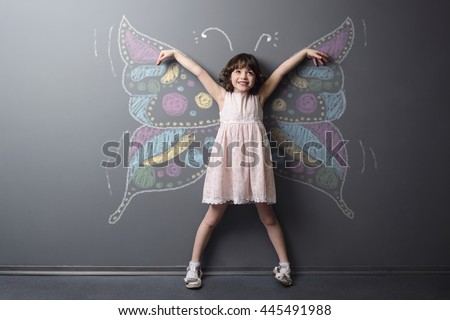 Funny little kid smiles with rised hands with the dream of being the butterfly. Huge depicted with chalk insect on the neutral background.