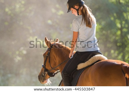 Young girl riding a horse  Royalty-Free Stock Photo #445503847