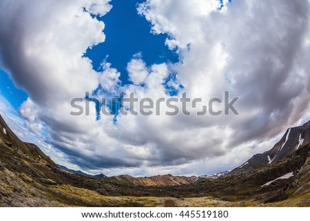 The picture was taken Fisheye lens. Travel to Iceland in July, volcanic summer tundra. Multi-colored rhyolite mountains - orange, yellow, green and blue