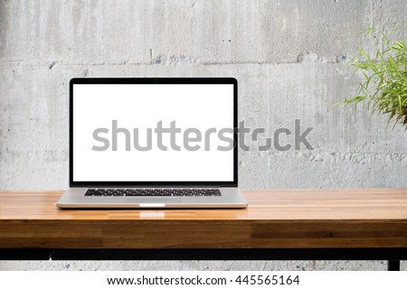 laptop blank screen on wooden table with concrete wall background