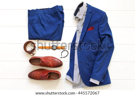 Flat lay set of classic men`s clothes such as blue suit, brown shoes, belt, watches and bracelet on white wooden background. Top view. Royalty-Free Stock Photo #445572067
