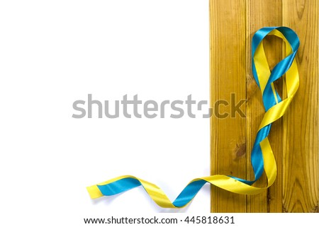 Yellow and blue satin ribbons on a wooden background #445818631