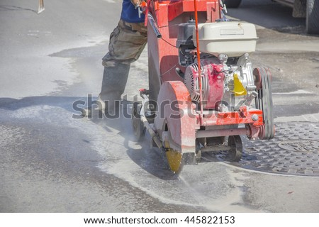 Construction worker cutting Asphalt paving stabs for sidewalk using a cut-off saw. Profile on the blade of an asphalt or concrete cutter with workers shoes and protective gear. #445822153