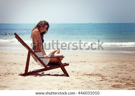 Young brunette woman sitting on the beach, looking at the sea. Summer photo. Vietnam. #446031010