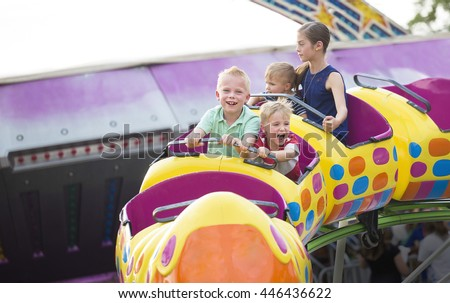 Kids on a thrilling roller coaster ride at an amusement park  Royalty-Free Stock Photo #446436622