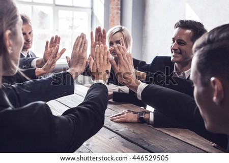 Business people give high five at business meeting #446529505