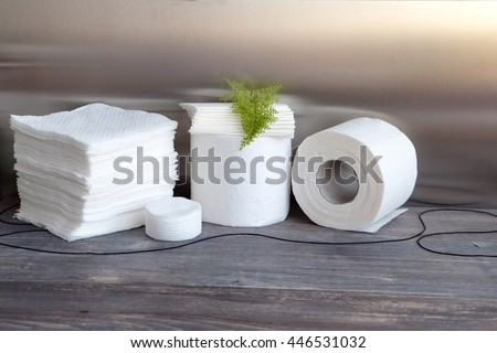 White kitchen paper towel, toilet paper, paper tissues, cotton pads on a wooden table #446531032