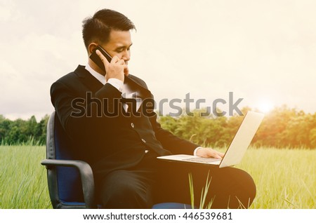 Manager, Business man sitting at a chair in the middle of a meadow in suit. #446539681