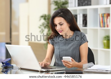 Executive working on line with a laptop and phone in a desktop at office #446585176