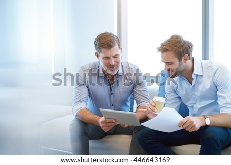 Handsome mature business manager using a digital tablet to discuss something positive with a young employee in a modern business lounge #446643169