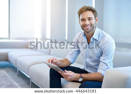 Portrait of a handsome young businessman sitting on a modern couch, holding a digital tablet, and smiling broadly at the camera #446643181