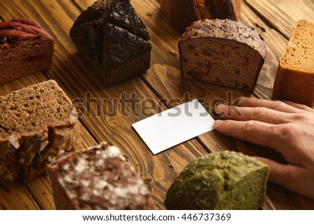 Hand takes blank business card of professional artisan baker presented in center of many mixed alternative baked exotic bread samples above wooden rustic table