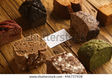 Blank business card of professional artisan baker presented in center of many mixed alternative baked exotic bread samples