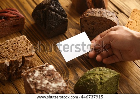 Blank business card of professional artisan baker presented in hand in center of many mixed alternative baked exotic bread samples above wooden rustic table