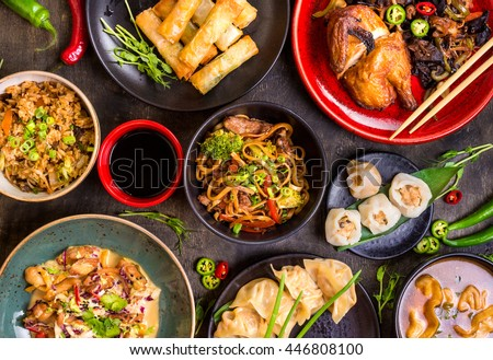 Assorted Chinese food set. Chinese noodles, fried rice, dumplings, peking duck, dim sum, spring rolls. Famous Chinese cuisine dishes on table. Top view. Chinese restaurant concept. Asian style banquet Royalty-Free Stock Photo #446808100