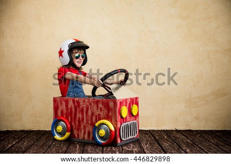 Child driving a car made of cardboard box. Kid having fun at home. Travel and summer vacation concept #446829898