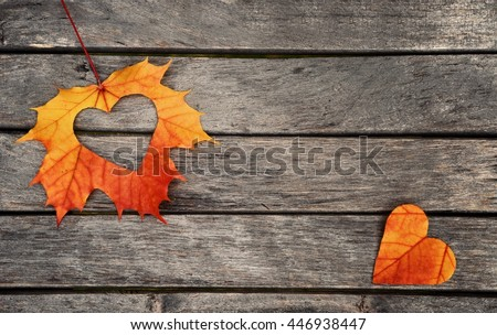 Autumn red and orange leaves with heart.  Fall wooden background.  #446938447