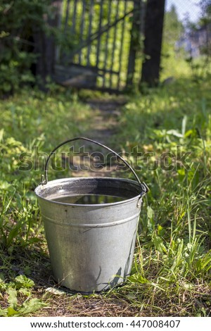 metallic bucket with pure drinking water stands on the footpath in the kitchen garden the background wicket and a fence #447008407