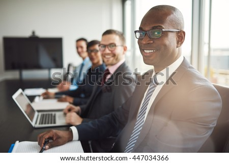 Smiling confident African businessman in a meeting with a group of multiracial co-workers seated at a conference table in the office #447034366