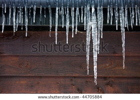 Icicles hanging from a drainpipe on the exterior of a wooden panelled house. Royalty-Free Stock Photo #44705884