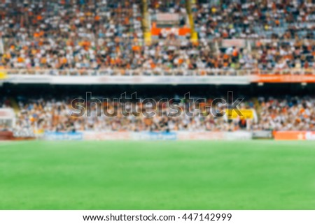 Unrecognizable football fans on tribunes watching game. Blurred. Useful as a background. Copy space area Royalty-Free Stock Photo #447142999