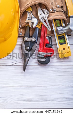 Leather tool belt building helmet on wooden board construction concept. #447151969