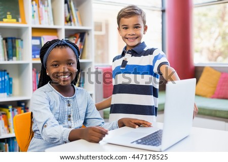 Portrait of smiling school kids using a laptop in library at school #447178525
