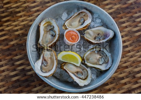 Raw Malpaque oysters on ice with lemon and seafood sauce. #447238486