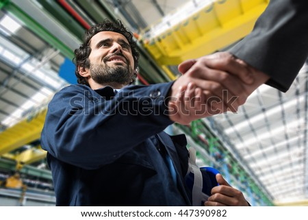 Portrait of a man giving an handshake in an industrial facility