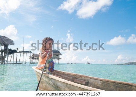 SEMPORNA, MALAYSIA - MAY 10 2016; Wonderful portrait of Sea gypsy girl  on a wooden canoe with crystal clear water in Sabah, Malaysia. Amazing seascape with clear sky and beautiful island background. #447391267