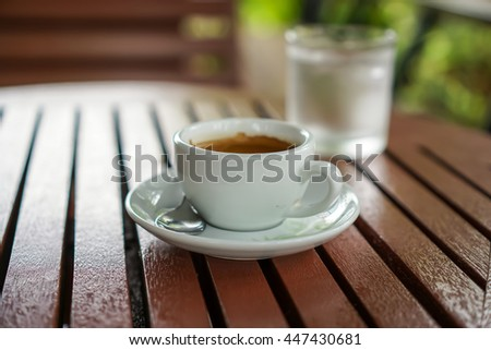 Soft focus and out of focus cup of coffee break and cold water background on wood table in coffee shop and nature background  #447430681