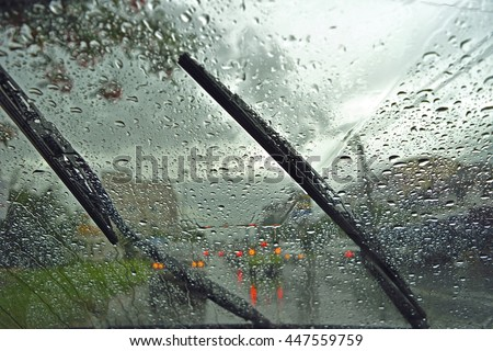 Windshield wipers from inside of car, season rain. traffic jam. Royalty-Free Stock Photo #447559759