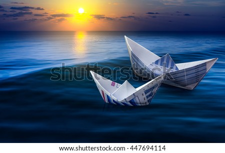 Two boats made from business paper graph on sea with sun light and sky. For financial ideas concept. #447694114