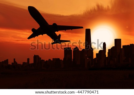 Airplane on sunset sky, plane flying over a city during sunrise    #447790471
