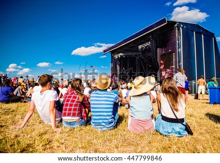 Teenagers, summer music festival, sitting in front of stage Royalty-Free Stock Photo #447799846