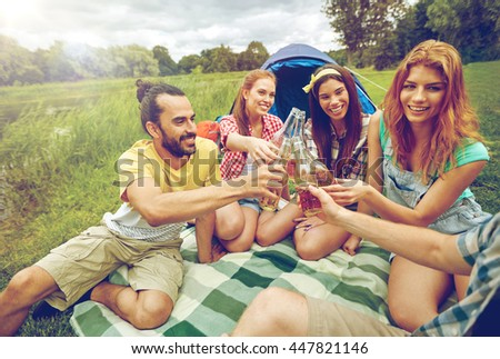camping, travel, tourism, hike and people concept - happy friends with glass bottles drinking cider or beer at campsite #447821146