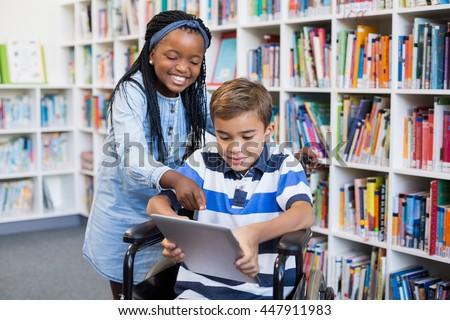 Happy schoolgirl standing with schoolboy on wheelchair using digital tablet in library #447911983