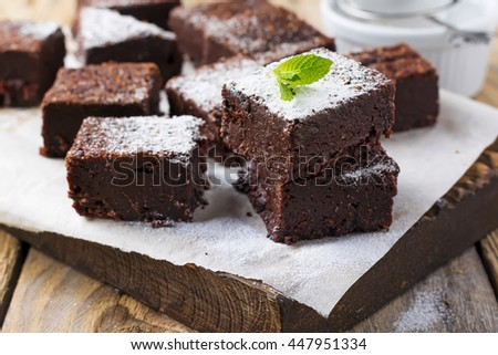 Chocolate brownies with powdered sugar and cherries on a dark wooden background. Selective focus. #447951334