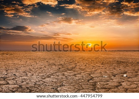 Global worming concept - cracked scorched earth soil drought desert landscape dramatic sunset Royalty-Free Stock Photo #447954799