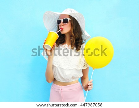 Fashion pretty young woman wearing a straw hat, sunglasses with air balloon drinks fruit juice from cup over colorful blue background #447987058